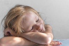 Op een grijze achtergrond ligt een slaap glimlachend meisje in de stralen van de zonochtend stock fotografie