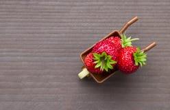 Op een grijze houten kruiwagen als achtergrond met bessen rode aardbeien plaatsen de aardbeien inschrijving royalty-vrije stock afbeelding