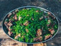 Op een groot ijzer voerde de plaat met gedobbeld, geroosterd op het vlees van het grillvarkensvlees en bestrooid met dille en pet Stock Foto's