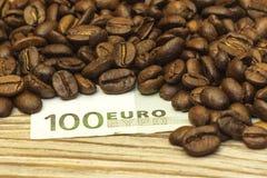 Op een houten achtergrond is een geldrekening en koffiebonen Stock Foto's