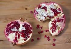 Op een houten lijst de twee helften van granaatappel het liggen Royalty-vrije Stock Foto