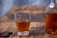 Op een houten lijst is een glas cognac, een snack van een stuk van donkere chocolade en een fles alcohol stock afbeeldingen