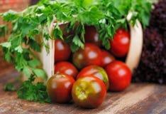 Op een houten lijst ligt mand met tomaat, sla stock afbeelding