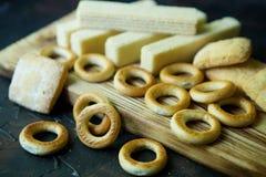 Op een houten Raad zijn ongezuurde broodjes, wafels en koekjes stock fotografie