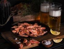 Op een houten raads zwarte plaat met garnalen Dichtbijgelegen glazen lichte bier en citroenwiggen stock fotografie