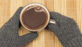Op een houten servet is er een mok met cacao, die langs indient de winterhandschoenen wordt gehouden stock foto's
