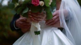 Op een huwelijksdag strijkt de bruidegom de bruid` s hand, het huwelijksboeket stock footage