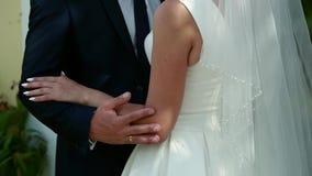 Op een huwelijksdag strijkt de bruidegom de bruid` s hand, het huwelijksboeket stock video