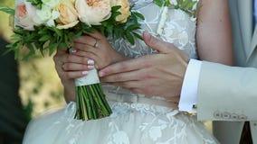 Op een huwelijksdag strijkt de bruidegom de bruid` s hand, het huwelijksboeket stock videobeelden