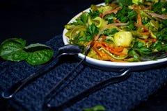 Op een langwerpige plaat is een schotel van courgette, wortelen, munt, kruiden, knoflook royalty-vrije stock afbeelding