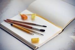 Op een open notitieboekje zijn borstels, potlood en waterverf in cuvettes royalty-vrije stock fotografie