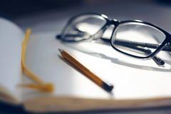 Op een open notitieboekje zijn glazen en een potlood stock foto's