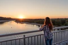 Op een pijler met staal bevindt het traliewerk zich over water meisjes jonge vrouw met haar terug met krullend haar bij zonsonder stock afbeeldingen