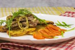 Op een plaat is geroosterd vlees met aardappels, wortelen en greens Stock Foto's