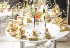 Op een plaat worden er canapes doordrongen met vleespennen, is het zeevruchten royalty-vrije stock afbeelding