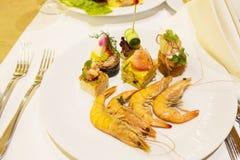 Op een plaat zijn vier garnalen, vijf canapés, groenten, aardappels royalty-vrije stock foto