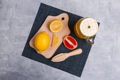 Op een raad is gesneden citroen en grapefruit, een handbediende juicer, naast een limonade in een kruik royalty-vrije stock afbeeldingen