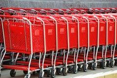 Op een rij stapelend rood boodschappenwagentje stock afbeeldingen