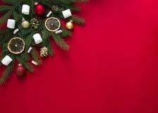 Op een rode achtergrond van groene die spartakken met Kerstmispeperkoek, gouden kegels, sinaasappelen, heemst en ballen worden ve Stock Afbeelding
