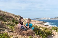 Op een rots op de kust in een reusachtig nest met eieren zit twee meisjes gekleed in de greephanden van feevogels en kijk ogen in Royalty-vrije Stock Afbeelding
