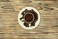 Op een schotel met koffiebonen is er een kop met koffiebonen Stock Foto