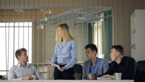 Op een vergadering van mannelijke collega's neem een vrouw, en zij werpt het document in de lucht stock footage