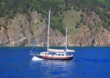 Op een vlotte blauwe oppervlakte van Meer Baikal van een berg met een blauwe hemel stock fotografie