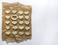 Op een wit ligt de achtergrond op bakseldocument een koekje in de vorm van een hart en één plaats is leeg Royalty-vrije Stock Afbeelding