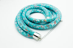 Op een wit ligt de achtergrond een halsband op de hals met een blauwe gem Stock Foto's