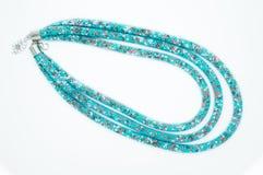 Op een wit ligt de achtergrond een halsband op de hals met een blauwe gem Stock Fotografie