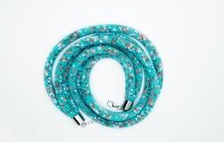 Op een wit ligt de achtergrond een halsband op de hals met een blauwe gem Royalty-vrije Stock Foto's