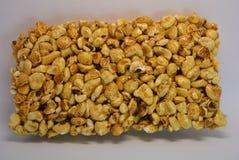 Op een Witboek wordt de achtergrond gevestigd en van het heerlijke en zoete roosteren van de pitten van het luchtgraan, popcorn m stock foto's