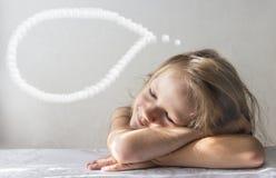 Op een witte achtergrond ligt een meisje van de slaap glimlachend droom in de stralen van de het exemplaarruimte van de zonochten royalty-vrije stock afbeelding