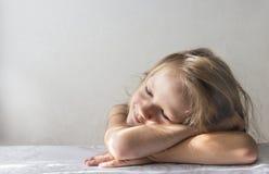 Op een witte achtergrond ligt een slaap glimlachend meisje in de stralen van de het exemplaarruimte van de zonochtend stock foto's