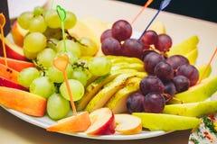 Op een witte plaat gesneden appelen en druiven Royalty-vrije Stock Fotografie