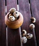 Op eieren van een de houten lijst rassypapy kwartel Stock Fotografie