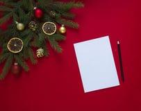 Op groene nette die takken rode als achtergrond met Kerstmispeperkoek, gouden kegels, sinaasappelen en ballen worden verfraaid Royalty-vrije Stock Foto's