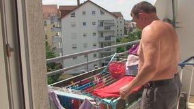 Op het balkon de man dingen neemt droogde gewassen uit stock footage