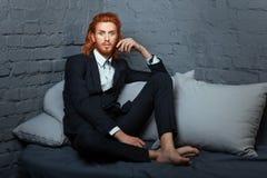Op het bed een mens met sproeten en rood haar Stock Foto's