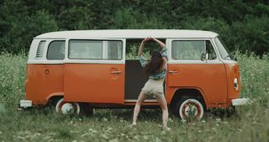 Op het bloemgebied het professionele dansersdame dacing verbazen voor een retro bestelwagen, beweegt zij zeer charismatisch stock footage