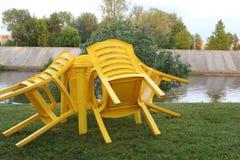 Op het gazon dichtbij de rivier is er een lijst met hellende stoelen na de regen stock afbeeldingen