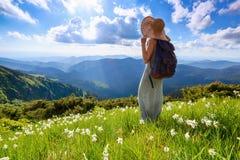 Op het gazon van witte gele narcissenbloemen het hipstermeisje die met achterzakverblijven van de zonsondergang genieten Ochtendl Stock Afbeeldingen