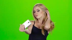 Op het het blondemeisje die van de smartphonecamera selfie doen Het groene scherm stock videobeelden