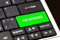 Op het laptop toetsenbord de groene knoop geschreven GOEDGEKEURD FDA Stock Foto