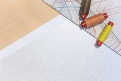 Op het lijstdocument met tekeningen van kleren, en naaiende draad De ruimte van het exemplaar stock afbeeldingen