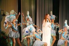 Op het overlegstadium in een witte kleding, de hoofdzanger van de bandmunt, extravagante vocalist Anna Malysheva Rood Royalty-vrije Stock Foto's