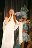 Op het overlegstadium in een witte kleding, de hoofdzanger van de bandmunt, extravagante vocalist Anna Malysheva Rood Stock Foto