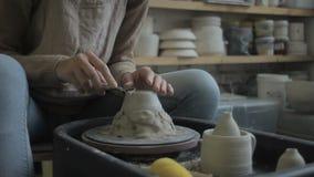 Op het pottenbakkers` s wiel maakt de beeldhouwer een vorm op een kleistuk stock videobeelden