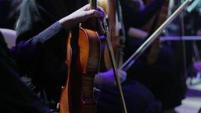 Op het stadium van het theater, houden de musici van het symfonieorkest violen in hun handen vóór de prestaties stock footage