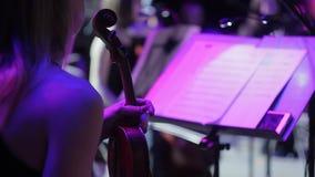 Op het stadium van het theater, houdt een vrouwenviolist van een symfonieorkest violen in haar handen vóór de prestaties stock video